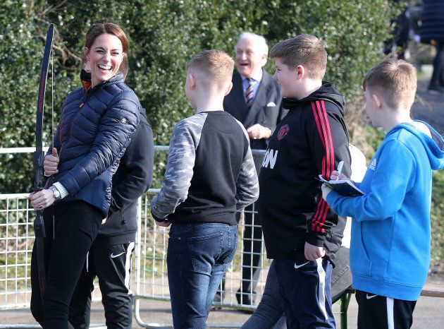 Kate Middleton enjoys a moment with some kids as she tries some archery at Roscor Youth Village in Fermanagh, Northern Ireland.