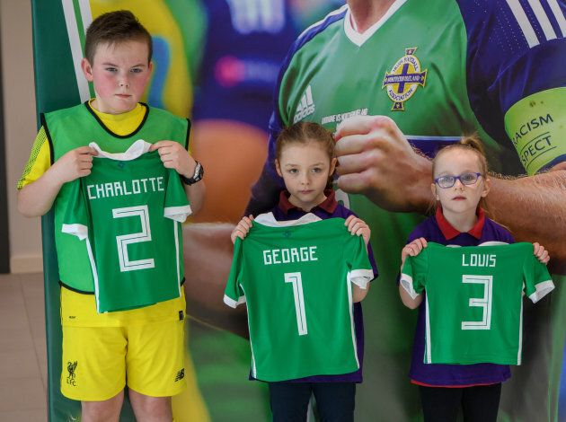 Catherine, Duchess of Cambridge and Prince William, Duke of Cambridge are given football shirts for their...