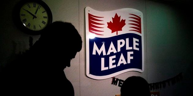 A Maple Leaf Foods employee, right, signs in a person from the media at the company's meat facility in...