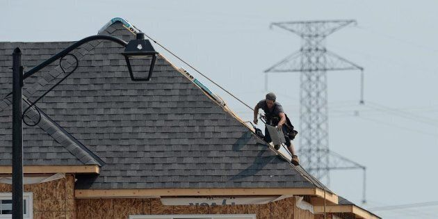 A construction worker shingles the roof of a new home in a development in Ottawa on July 6,