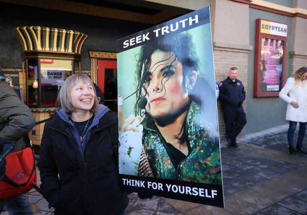 """Brenda Jenkyns, who drove from Calgary, stands with a sign outside of the premiere of the """"Leaving Neverland,"""" during the 2019 Sundance Film Festival, Friday, Jan. 25, 2019, in Park City, Utah."""