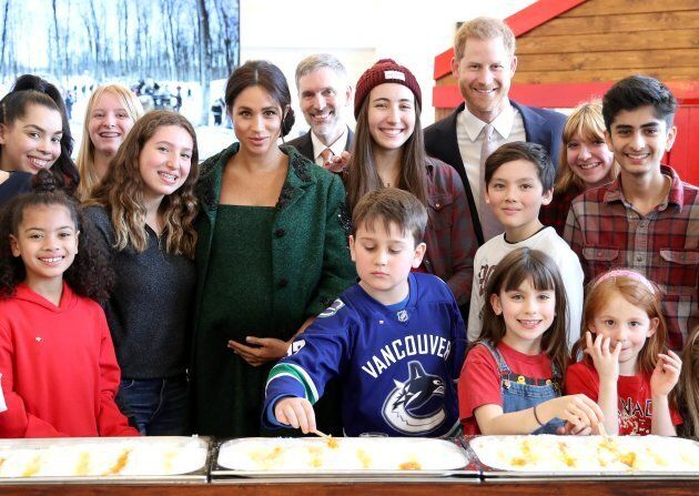 Harry and Meghan pose with kids. Check out that hero in the