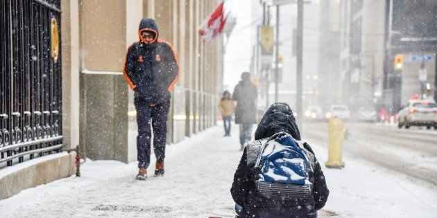 A homeless person tries to stay warm by an underground exhaust vent while trying to collect change from a passing pedestrian on Bay Street in Toronto on Jan. 19, 2019.