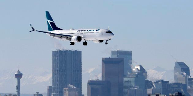 A Boeing 737 MAX 8 jetliner, belonging to WestJet Airlines, passes the downtown skyline as it lands in...