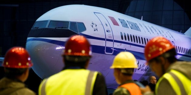 Workers attend a ceremony marking the first delivery of a Boeing 737 Max 8 airplane to Air China in Zhoushan,...