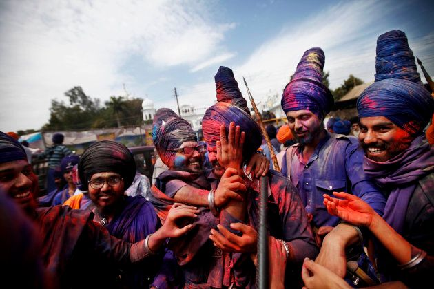 Nihangs (Sikh warriors) smear each other's faces with colour powder as they participate in a religious procession during the annual fair of Hola Mohalla in Punjab, India.