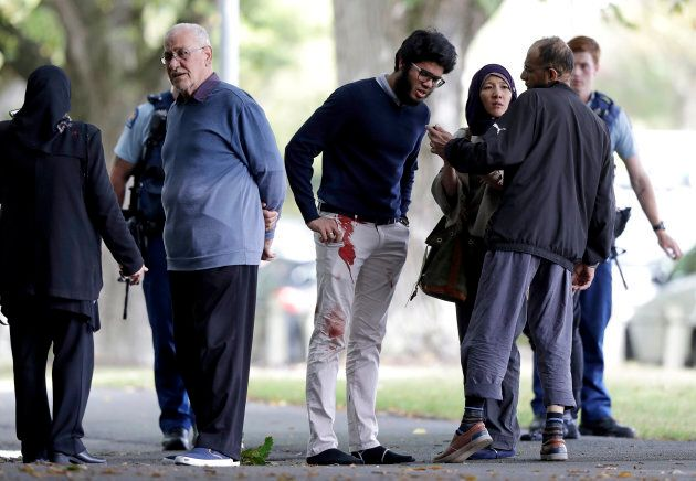 People stand across the road from a mosque in central Christchurch, New Zealand on Friday.