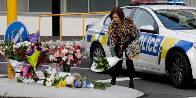 A woman places flowers at a make-shift memorial near the mosque in Christchurch, New Zealand on Saturday.