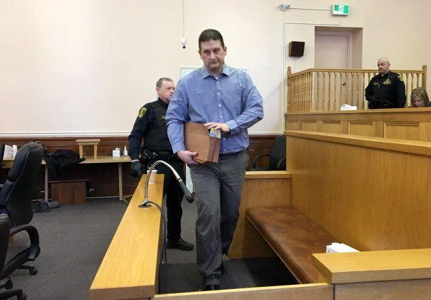 Trent Spencer Butt walks into the defendant's box at St. John's Supreme Court on