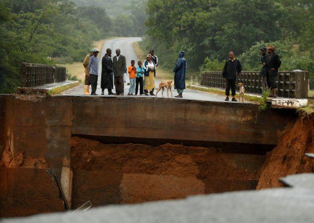 Locals look at a washed away bridge along Umvumvu river following Cyclone Idai in Chimanimani, Zimbabwe on March 18, 2019.