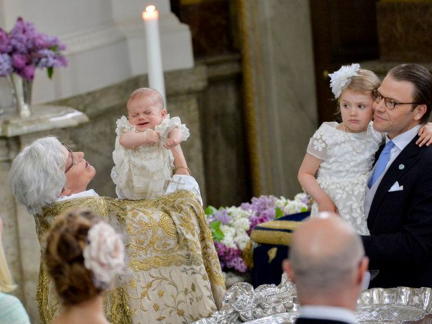 Arch Bishop Antje Jackela holds Prince Oscar  - who is NOT A FAN OF WATER, THANKYOUVERYMUCH - while Princess Estelle and Prince Daniel look on at the christening on May 27, 2016 at the Chapel in Stockholm's Royal palace.