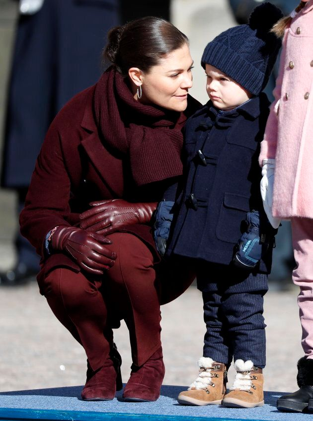 Crown Princess Victoria of Sweden, probably trying to bribe Oscar into smiling by promising him sweet, sweet candy after the ceremony. Prince Oscar, not taking the bait, holds out for a pony.