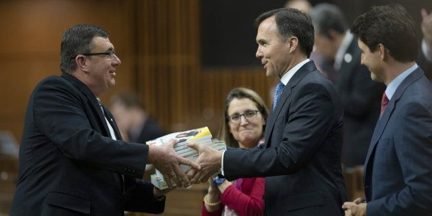 Prime Minister Justin Trudeau looks on as Finance MinisterBillMorneautables the federal budget documents...