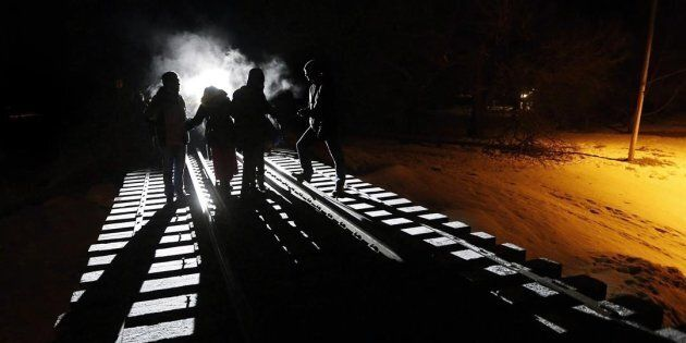 Eight migrants from Somalia cross into Canada illegally from the United States by walking down this train...