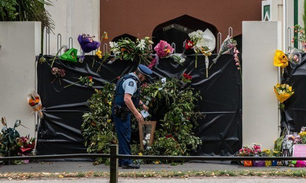A policeman places flowers on the gates of Al Noor mosque in Christchurch, New Zealand on March