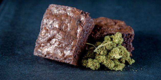 A stack of marijuana edible brownies next to a small pile of medical marijuana nugs. Black