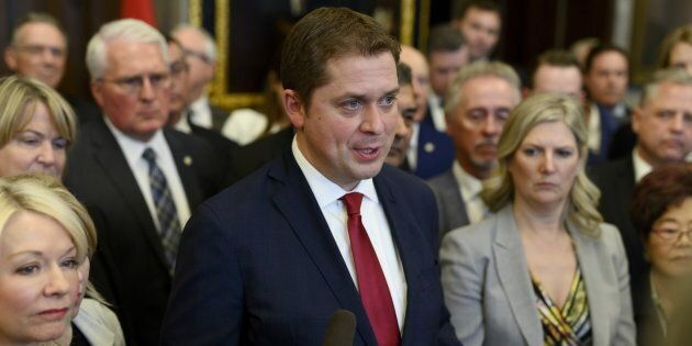 Conservative Leader Andrew Scheer speaks to reporters with his caucus surrounding him after leaving the...