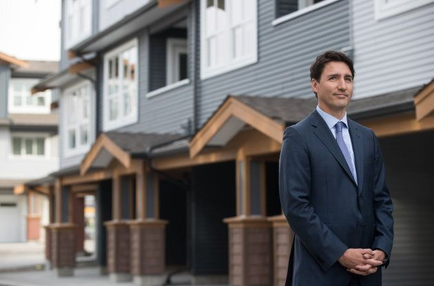 Trudeau listens while being introduced before a post-budget housing announcement at a townhouse development...