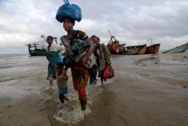 A displaced family arrives after being rescued by a boat from a flooded area of Buzi district, 200 kilometres...