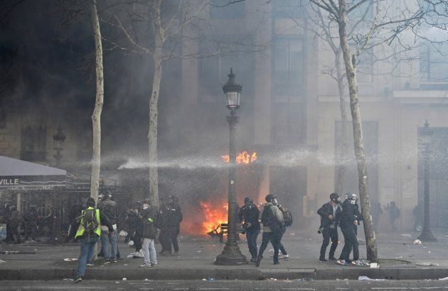 French riot police use water cannon to disperse yellow-vest protesters on the Champs-Elysees during the...