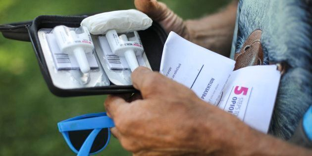 A Toronto man checks out a Naloxone kit he was given at a pop up safe-injection
