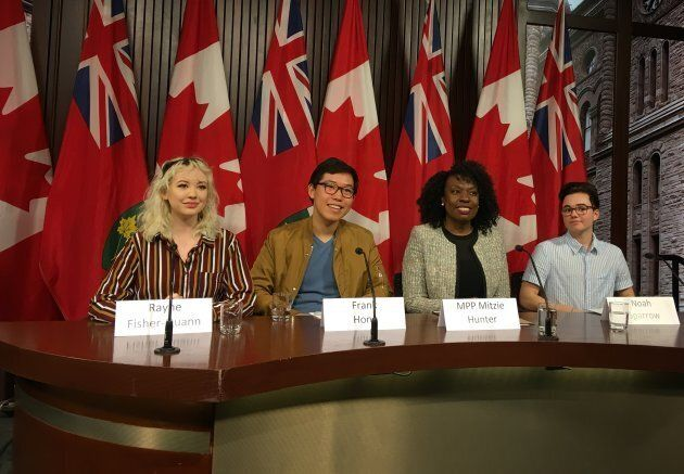 Students Rayne Fisher-Quann, Frank Hong and Noah Sparrow pose with Liberal MPP Mitzie Hunter at Queen's Park.