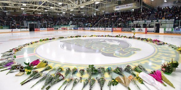 Flowers lie at centre ice as people gather for a vigil at the Elgar Petersen Arena, home of the Humboldt...