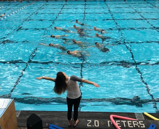Head coach Holly Hjartarson works with the men's synchronized swimming team in