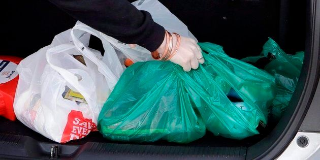 A shopper places her goods into her car outside a supermarket in Christchurch, New Zealand, on Aug. 10,
