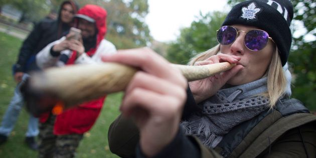 A woman smokes a somewhat oversized marijuana cigarette during a legalization party at Trinity Bellwoods...