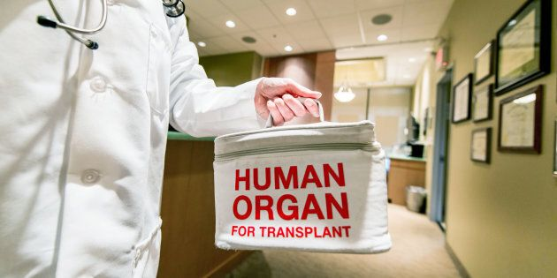 A doctor taking or delivering a bag containing a human organ for