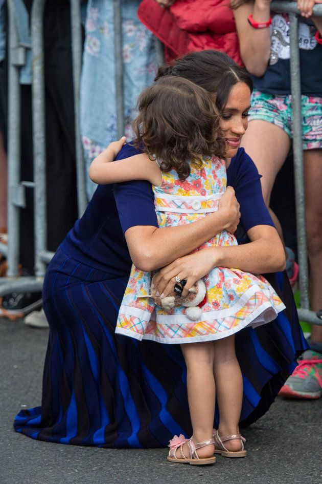 The Duchess of Sussex hugs a young girl during a walkabout in Rotorua on day four of the royal couple's...