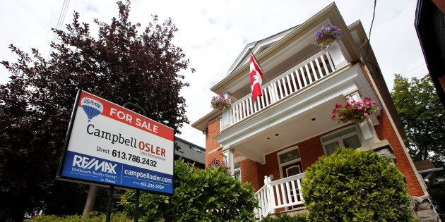 A real estate sign is seen in front of a house for sale in Ottawa, Aug. 15,