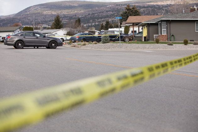 RCMP officers work outside a crime scene in Penticton, B.C., on April 15,