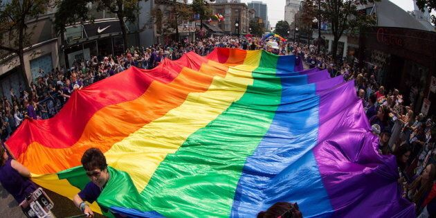 A giant rainbow flag is carried on Robson Street during the Vancouver Pride Parade on August 6, 2017. The Royal Canadian Mint says it plans to celebrate a 1969 government act that