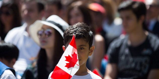 A young boy holds a Canadian flag while watching a special Canada Day citizenship ceremony in West Vancouver,...