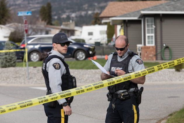 RCMP officers escort a neighbour as they work outside of a crime scene in Penticton, B.C., on April 15,