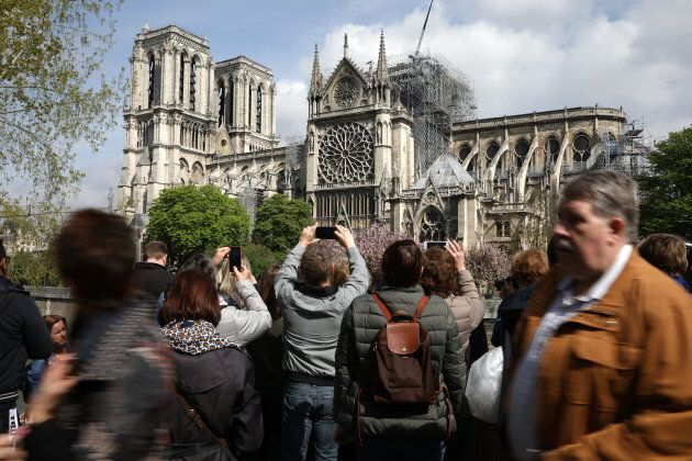 Tourists and locals take pictures of the Notre Dame Cathedral on April 17, 2019. The island that houses...