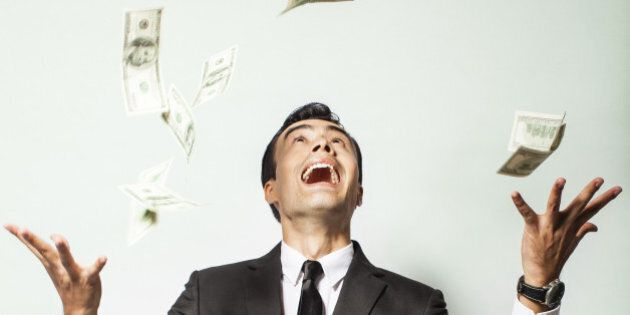Businessman rejoicing for his success with hundred dollar bills. Money rain
