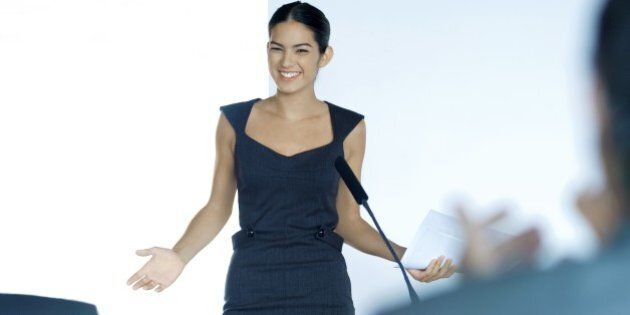 Businesswoman speaking with microphone during