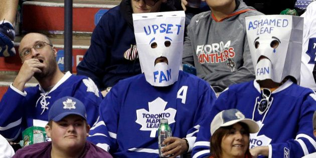 Toronto Maple Leafs fans wear bags over their heads in the third period of an NHL hockey game against...