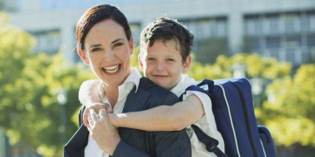 Businesswoman and son hugging in urban
