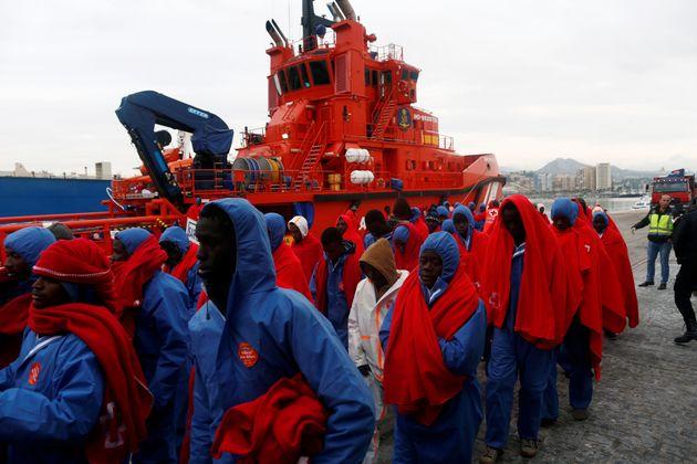 Des migrants, interceptés au large de la mer Méditerranée, marchent après...