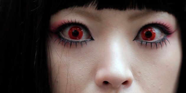 A woman puts on red contact lenses at a Halloween event in Kawasaki, near Tokyo, Sunday, Oct. 28, 2012.(AP...