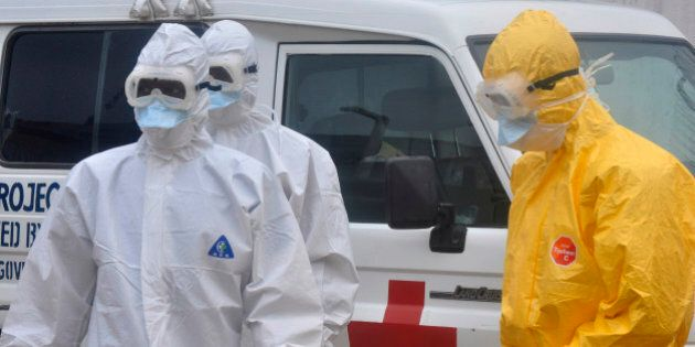 Health workers in protective gear wait to carry a body of a person suspected to have died from Ebola...
