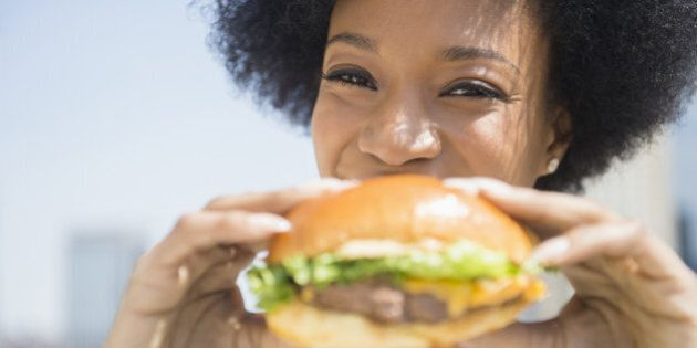 African American woman eating cheeseburger