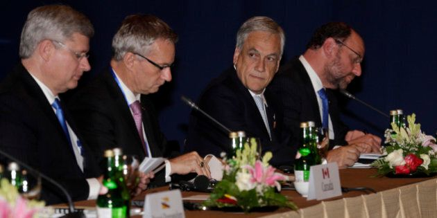 Chilean President Sebastian Pinera, second left, and Canadian Prime Minister Stephen Harper, left, attend the Trans-Pacific Partnership meet in Bali, Indonesia, Tuesday, Oct. 8, 2013. Leaders of the dozen countries involved in the U.S.-led Trans-Pacific Partnership met in Bali after the Asia-Pacific Economic Cooperation (APEC) summit to work on plans for a free trade area they hope will eventually encompass the entire region. (AP Photo/Wong Maye-E)