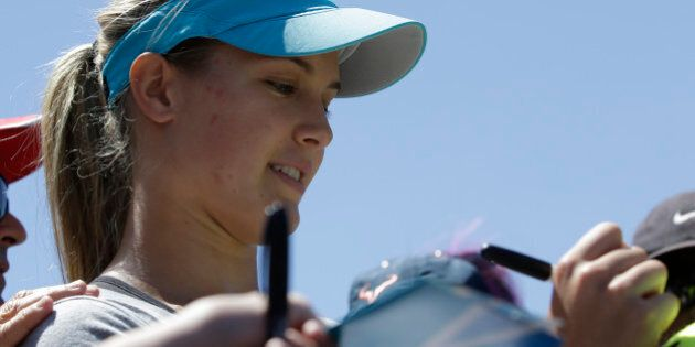 Eugenie Bouchard of Canada signs autographs for fans during a training session at the Australian Open tennis championship in Melbourne, Australia, Wednesday, Jan. 22, 2014.  Bouchard faces Li Na of China in the women's singles semifinal Thursday.(AP Photo/Aijaz Rahi)