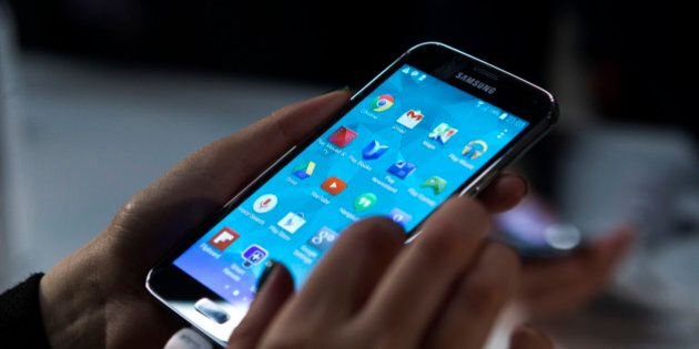 Attendees inspect Galaxy S5 smartphones on display during a Samsung Electronics Co. news conference on...