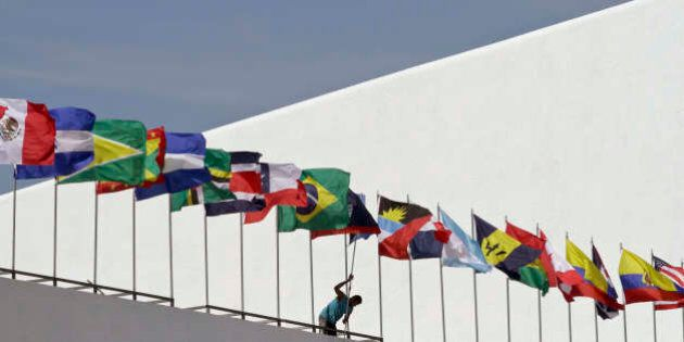A worker paints a wall below a set up of the flags of the countries that will participate in the upcoming...